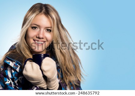 Young woman holding cup of hot chocolate with marshmallows - stock photo
