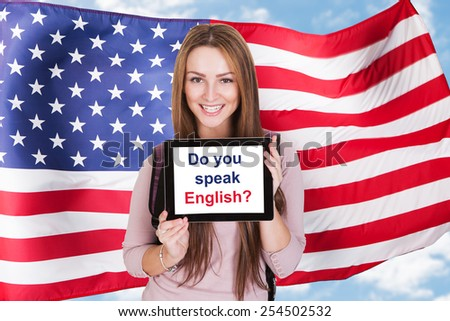 Young Woman Holding Digital Tablet Asking Do You Speak English In Front Of Usa Flag - stock photo