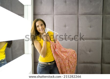 Young woman holding dress on hanger, smiling, portrait - stock photo
