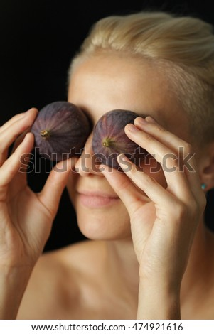 Young woman holding figs fruit in her hand near face