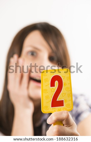 Young woman holding figure two in her hand - stock photo