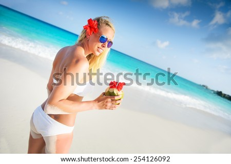 Young Woman Holding Fresh Cold Coconut At Tropical Beach - stock photo