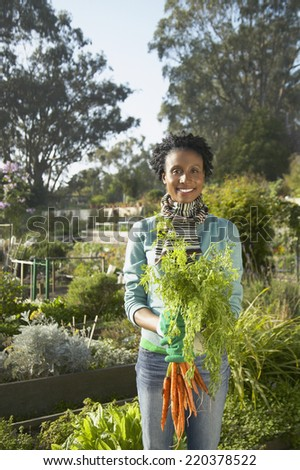 Young woman holding freshly picked plants for the camera - stock photo