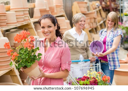 Young woman holding geranium in clay pot at garden center
