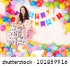 Young woman holding gift box at birthday party. - stock photo