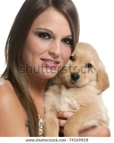 Young woman holding Golden Retriever puppy in front of white background