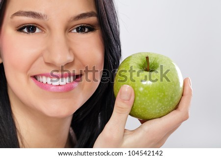 Young woman holding green apple and smiling - stock photo