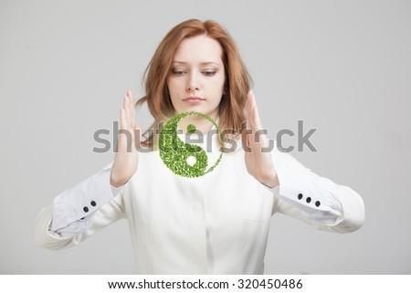 Young woman holding green plant ying yang symbol - stock photo