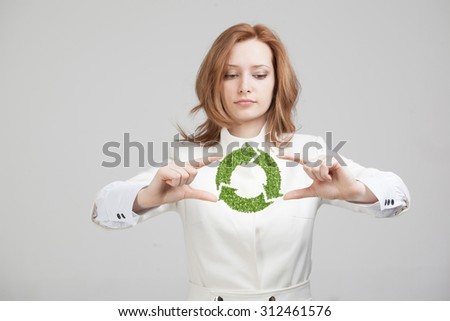 Young woman holding green recycle symbol in his hands - stock photo