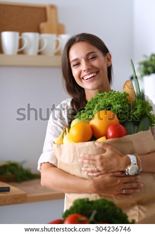 Young woman holding grocery shopping bag with vegetables and fruit .  - stock photo