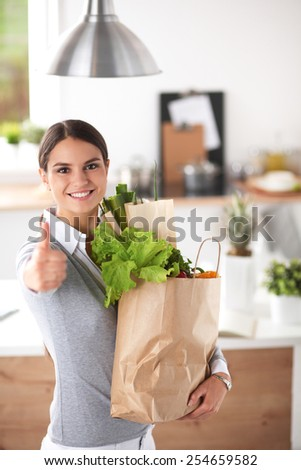Young woman holding grocery shopping bag with vegetables and showing ok - stock photo