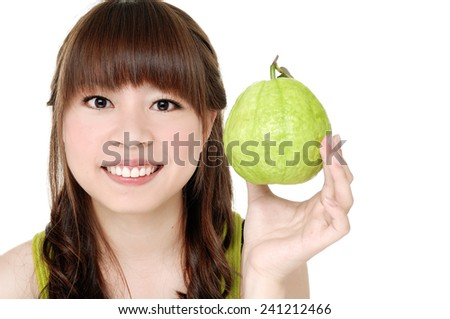 young woman holding guava fruit-close up - stock photo