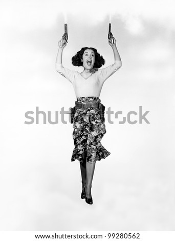 Young woman holding handguns and jumping - stock photo