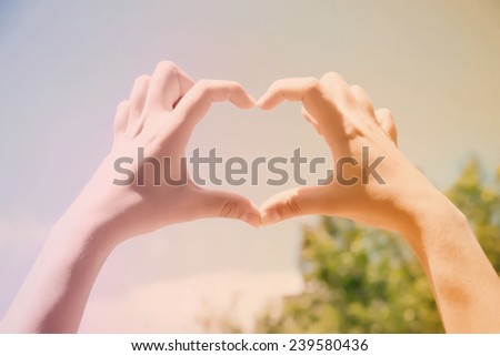 Young woman holding hands in heart shape framing on blue sky background - stock photo