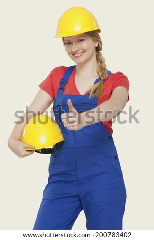 Young woman holding hard hat showing thumbs up sign - stock photo
