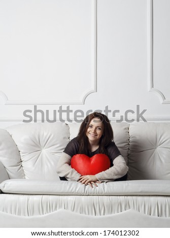 Young woman holding heart in her hands - stock photo