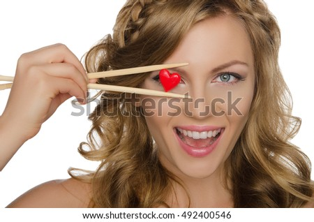 young woman holding heart with chopsticks isolated on white