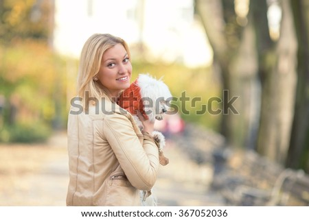 Young woman holding her cute Maltese terrier looking at camera over the shoulder