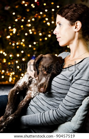 Young woman holding her dog at Christmas time - stock photo