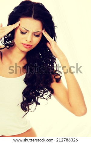 Young woman holding her head in pain suffering from a headache,migraine, stress, insomnia or hangover - stock photo