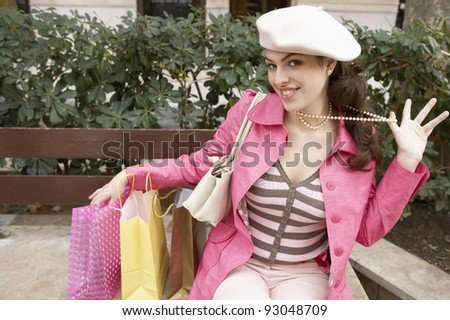 Young woman holding her pearl necklace while sitting down with shopping bags. - stock photo