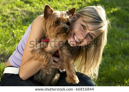 Young woman holding her pet dog - stock photo