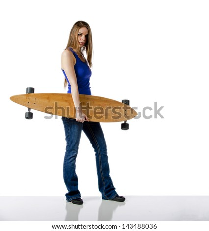 Young woman holding her skateboard on a white background with a reflective floor. - stock photo