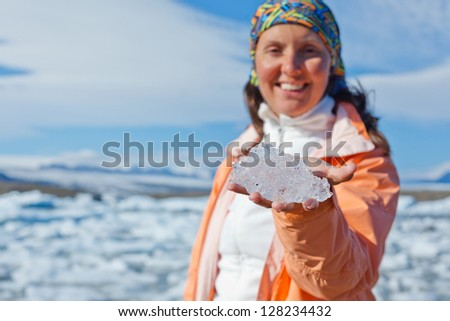 Young woman holding ice. Focus on the piece of ice. Jokulsarlon a lake in Iceland where icebergs collapsing from Vatnajokull glacier are floating around. - stock photo