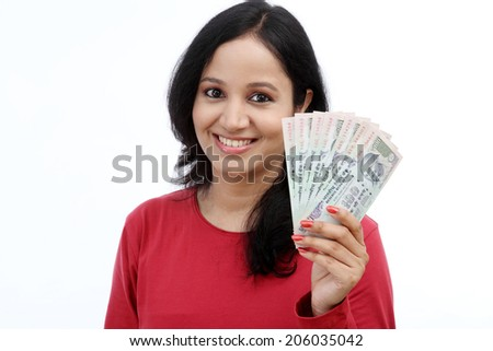 Young woman holding Indian rupee notes against white background