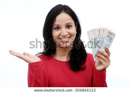 Young woman holding Indian rupee notes against white background - stock photo