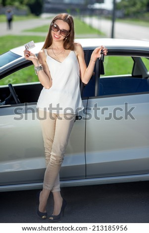Young woman holding keys to new car smiling at camera and sitting on the car door - stock photo