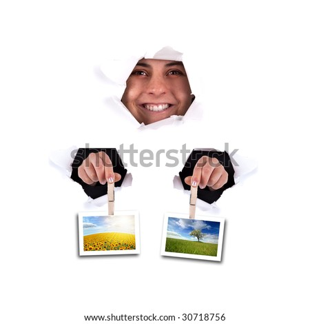 young woman holding landscape photos thru wall hole - square format - stock photo