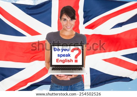 Young Woman Holding Laptop Asking Do You Speak English In Front Of British Flag - stock photo