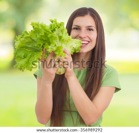 Young woman holding lettuce, green salad over nature background - stock photo