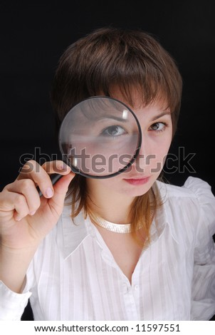 Young woman holding magnifying glass on black background - stock photo