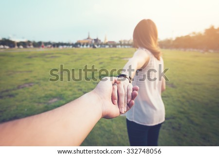 Young woman holding man hand on the greenfield. Focus on hands. traveller, vintage processed. - stock photo
