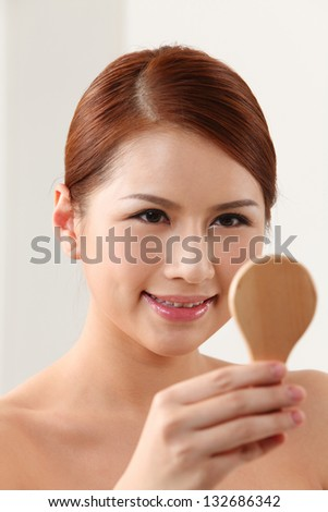 Young woman holding mirror on the white background - stock photo