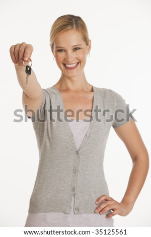 young woman holding out keys towards camera on white seamless background with selective focus - stock photo
