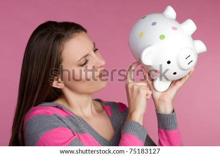 Young woman holding piggy bank - stock photo