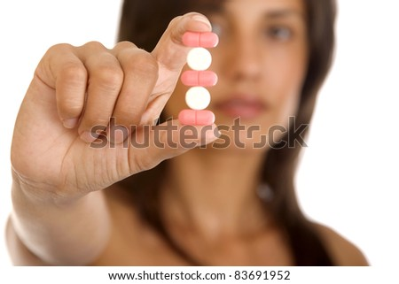 Young woman holding pills, isolated on white