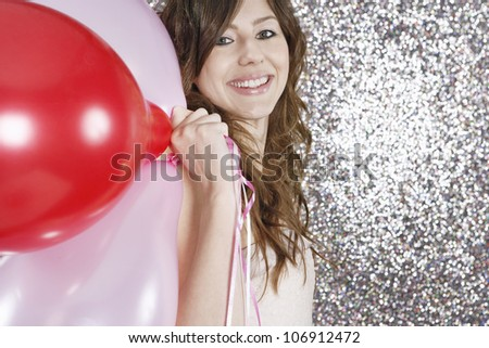 Young woman holding pink and red balloons and smiling at camera while standing against a silver glitter background.