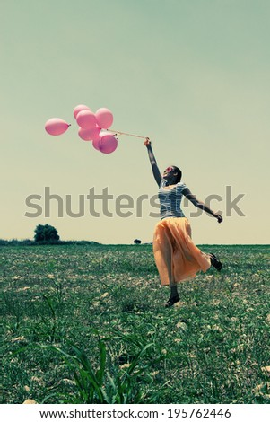 Young woman holding pink balloons and flying over a meadow. Photo in old color image style.