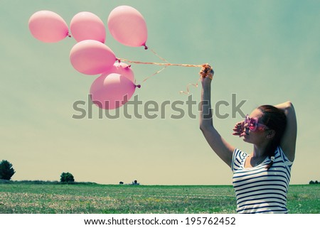 Young woman holding pink balloons and flying over a meadow. Photo in old color image style. - stock photo