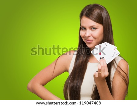Young Woman Holding Playing Cards against a green background
