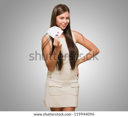 Young Woman Holding Playing Cards against a grey background - stock photo