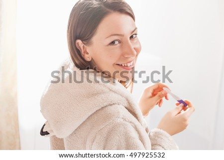 young woman holding pregnancy test