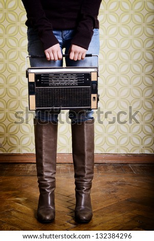 young woman holding radio player in room with vintage wallpaper, legs detail, retro stylization 60-70s, toned - stock photo