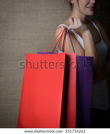 Young woman holding red and purple shopping bags over canvas, image toned. - stock photo