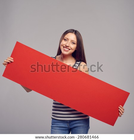 Young woman holding red blank cardboard over gray background - stock photo