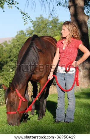 Young woman holding red lead rope while bay colored horse grazes on green grass. - stock photo